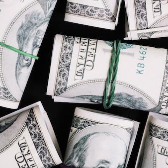 Uma visão aérea de enrolado nos nota de moeda de dólar em fundo preto