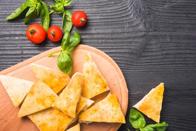 Uma visão aérea de fatias de pão com folhas de manjericão e tomate na mesa de madeira