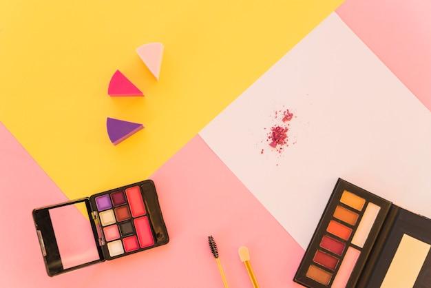 Uma visão aérea de ferramentas de maquiagem profissional e paleta de sombra em fundo colorido