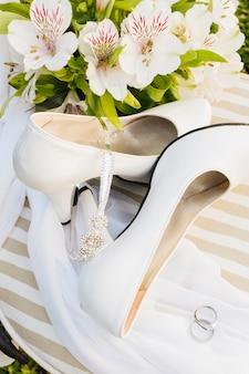 Uma visão aérea de flores; salto alto; coroa; cachecol e anéis de casamento na mesa
