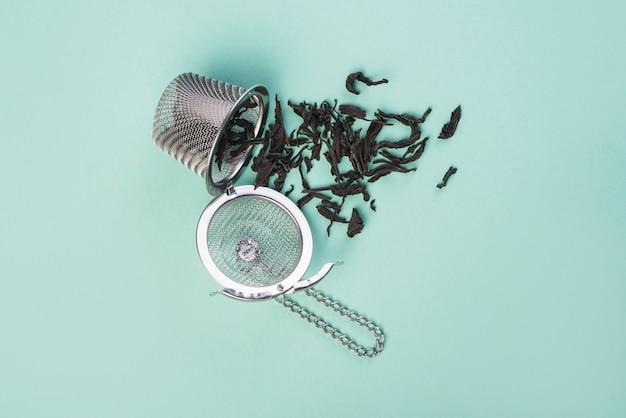 Uma visão aérea de folhas de chá secas caindo do coador