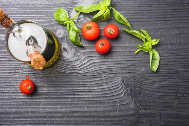 Uma visão aérea de folhas de manjericão; tomates e garrafa de azeite no pano de fundo de madeira