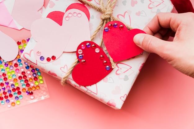 Uma visão aérea de forma de coração vermelho e rosa na caixa de presente embrulhado
