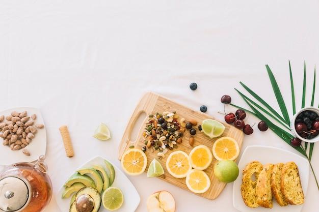 Uma visão aérea de frutas; chá; pão e frutas secas no fundo branco