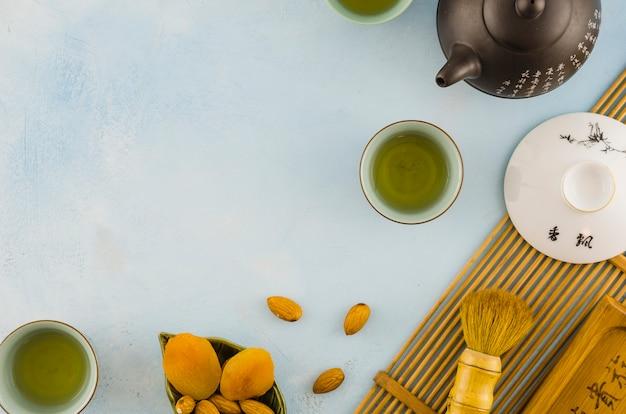 Uma visão aérea de frutas secas; xícaras de chá e bule no pano de fundo texturizado