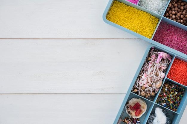 Uma visão aérea de grânulos coloridos em caixa azul na mesa de madeira branca