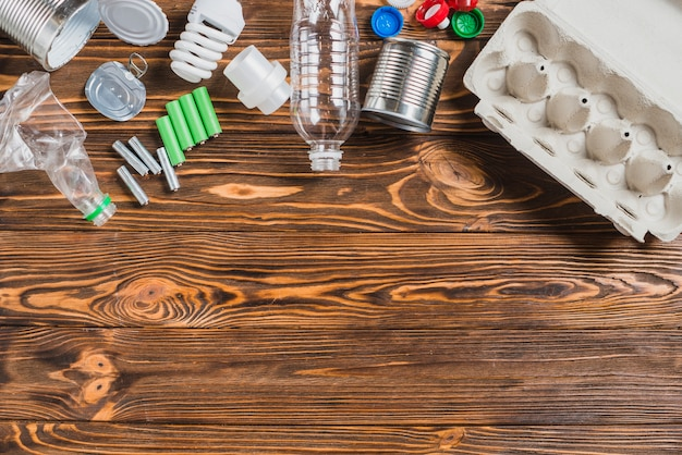 Uma visão aérea de itens de reciclagem no fundo de madeira marrom