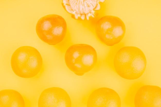Uma visão aérea de laranjas inteiras em pano de fundo amarelo