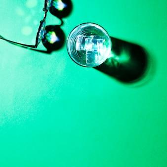Uma visão aérea de óculos e copo de água com sombra sobre fundo verde