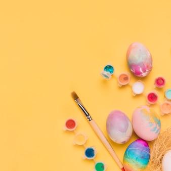 Uma visão aérea de ovos de páscoa pintados; pincel e tinta de cor de água no pano de fundo amarelo