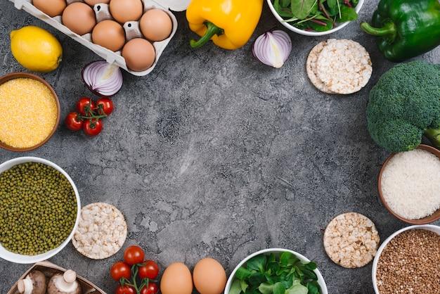 Uma visão aérea de ovos; legumes; tigela de polenta e feijão mung no cenário de concreto