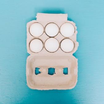 Uma visão aérea de ovos na caixa no fundo azul