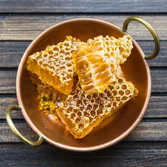 Uma visão aérea de peças de favo de mel no utensílio de cobre com alças