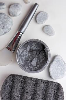 Uma visão aérea de pedras de spa; escova; máscara de argila; e pedra-pomes no fundo branco
