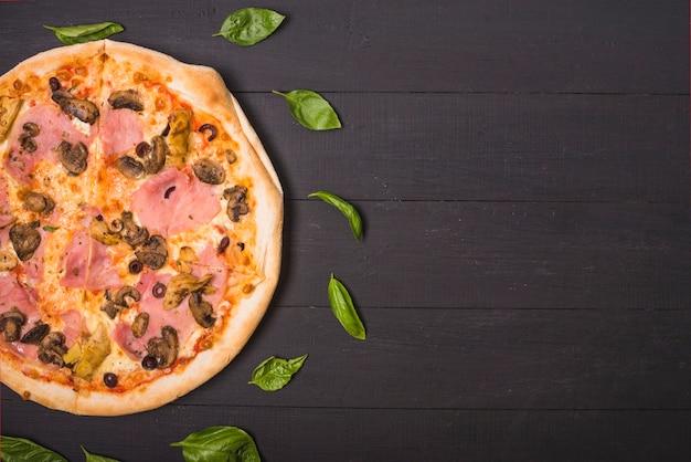 Uma visão aérea de pizza caseira decorada com folhas de manjericão na prancha de madeira