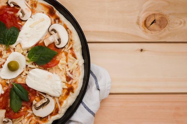 Uma visão aérea de pizza italiana em pano de fundo de madeira