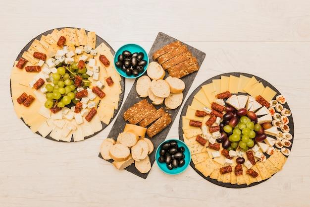 Uma visão aérea de prato de queijo com fatias de pão e azeitonas na mesa de madeira