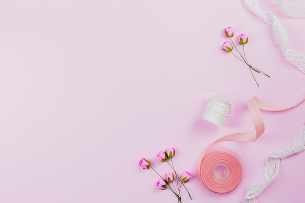 Uma visão aérea de rosas artificiais; carretel e fitas em fundo rosa