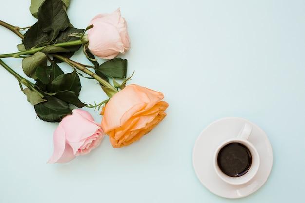 Uma visão aérea de rosas coloridas com xícara de café e pires em fundo azul