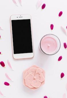 Uma visão aérea de sabão em forma de flor; vela e smartphone decorado com pétalas