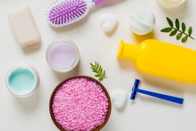Uma visão aérea de sal rosa com produtos cosméticos no fundo branco