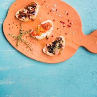 Uma visão aérea de sanduíches torradas com tomilho; pimenta e sal na tábua de cortar