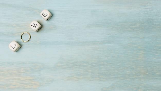 Uma visão aérea de texto feito com cubos e anel de casamento no canto do cenário de madeira