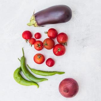 Uma visão aérea de tomates; pimentos verdes; cebola e berinjela no plano de fundo texturizado branco