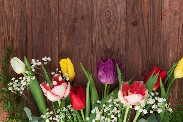 Uma visão aérea de tulipas frescas e flor de respiração do bebê na mesa de madeira