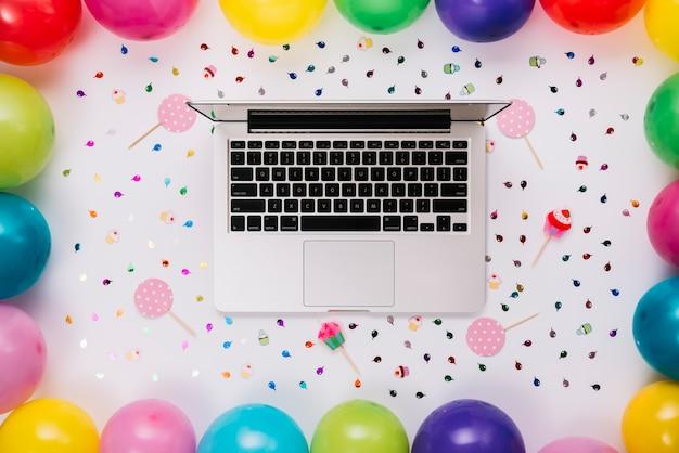 Uma visão aérea de um laptop aberto decorado com confetes; prop e balões coloridos em pano de fundo branco