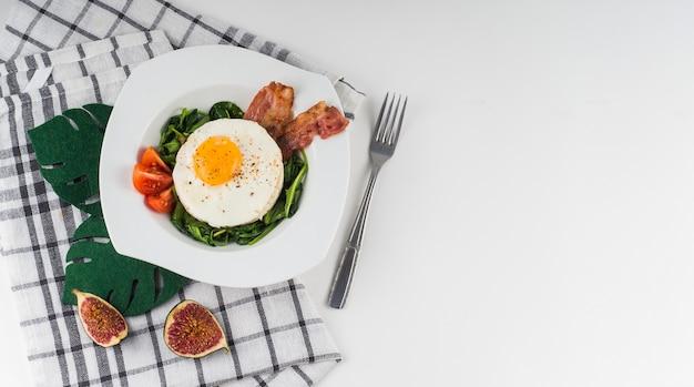 Uma visão aérea de um ovo frito com espinafre; tomate e bacon na chapa branca com guardanapo; garfo e figo fatia em fundo branco