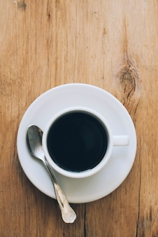 Uma visão aérea de uma xícara de café preto acabado de fazer no plano de fundo texturizado de madeira