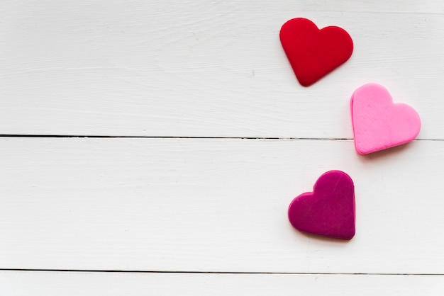 Uma visão aérea de vermelho; formas de coração-de-rosa e roxas na mesa texturizada branca