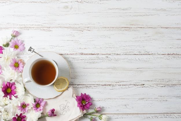 Uma visão aérea de xícara de chá de ervas com flores em pano de fundo texturizado de madeira pintada