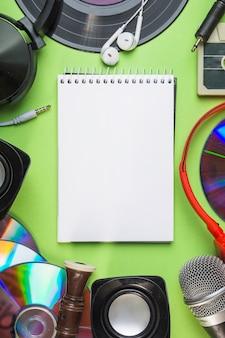 Uma visão aérea do bloco de notas espiral em branco com equipamentos de áudio
