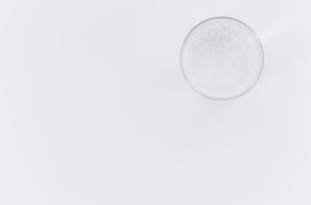 Uma visão aérea do copo de água no fundo branco com espaço para escrever o texto