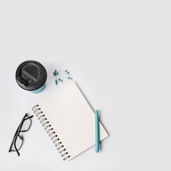 Uma visão aérea do copo de café descartável; alfinetes de pressão; caneta; óculos e bloco de notas em espiral no fundo branco