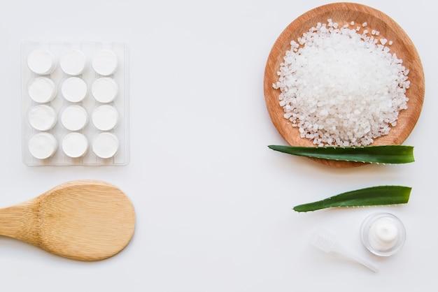 Uma visão aérea do creme hidratante com sal e aloevera deixa no fundo branco