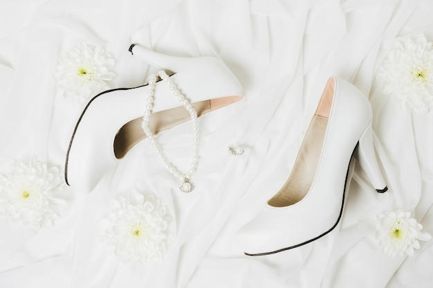 Uma visão aérea do crisântemo; colar; brincos e saltos altos do casamento no lenço branco