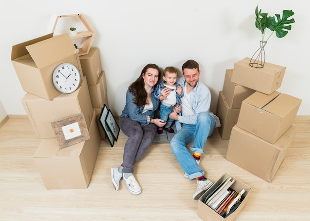 Uma visão aérea do jovem casal com seu bebê sentado entre caixas de papelão em sua nova casa