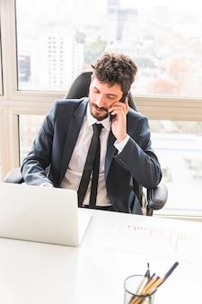 Uma visão aérea do jovem empresário falando no celular no local de trabalho