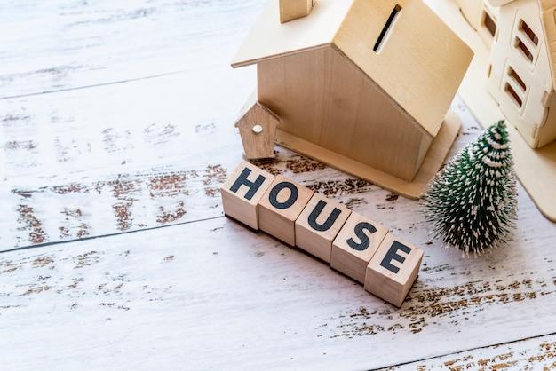 Uma visão aérea do modelo de casa com blocos de madeira da casa e árvore de natal na superfície texturizada branca