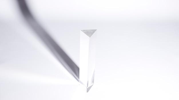 Uma visão aérea do prisma triangular com sombra escura sobre fundo branco