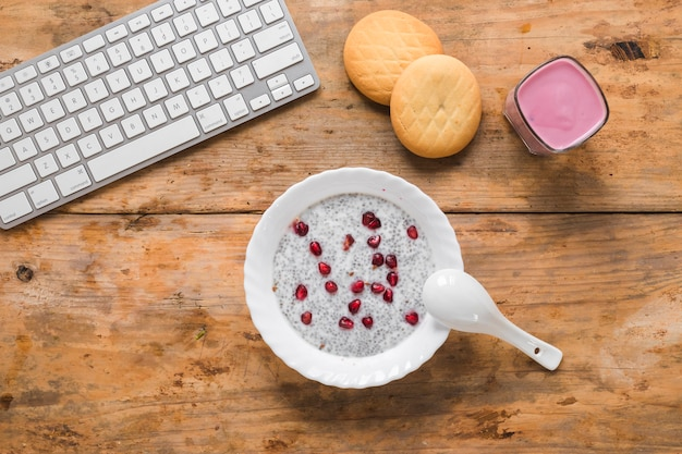 Uma visão aérea do pudim de sementes de chia; biscoitos; smoothie e teclado de computador sem fio na mesa
