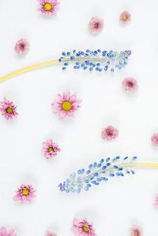 Uma visão aérea do rímel roxo e padrão de flor rosa no pano de fundo branco