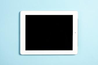 Uma visão aérea do tablet digital com tela em branco sobre fundo azul