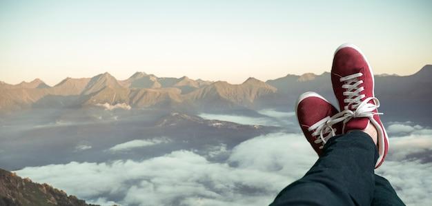 Uma visão bem acima de cima para baixo das pernas no quadro e observando a paisagem