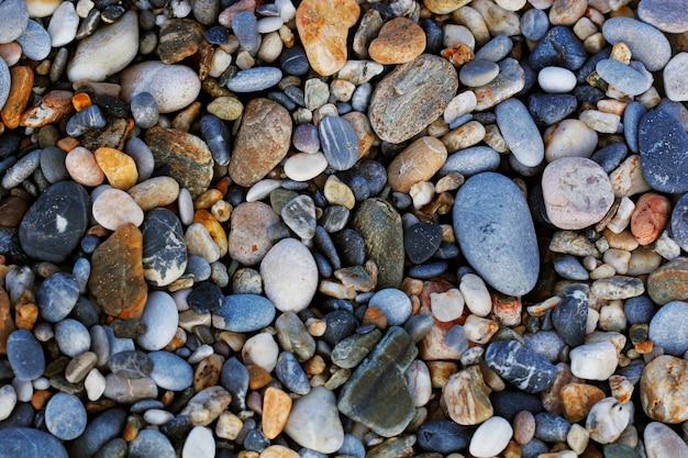 Uma visão de close-up de pedras multicoloridas polidas lisas lavadas em terra na praia.