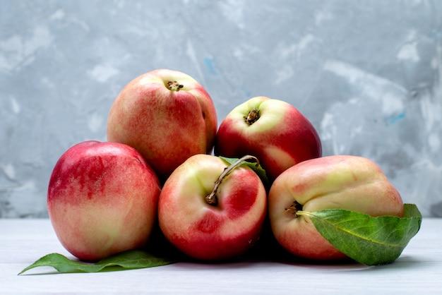 Uma visão de frente pêssegos frescos azedos e maduros no fundo branco cor de fruta suave