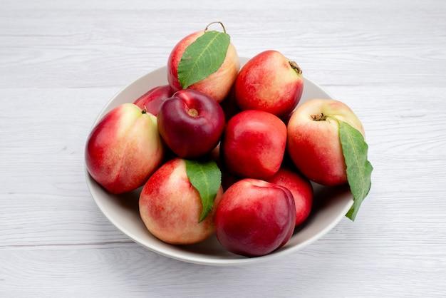 Uma visão de frente pêssegos frescos e maduros dentro da placa branca no fundo branco cor de frutas frescas